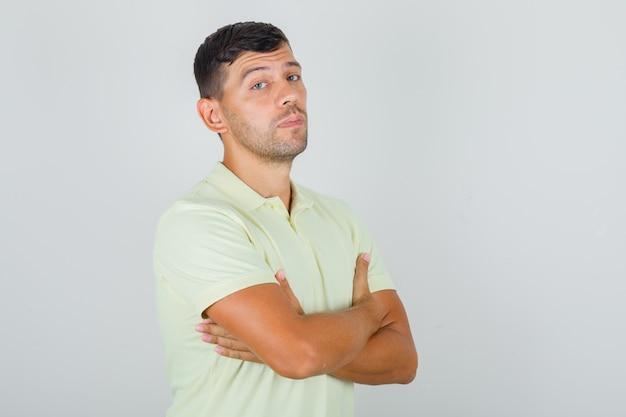 Man in geel t-shirt staan met gekruiste armen en op zoek naar beslissend