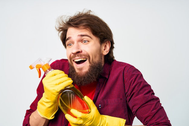 Man in gele handschoenen wasmiddel schoonmaken van het huis