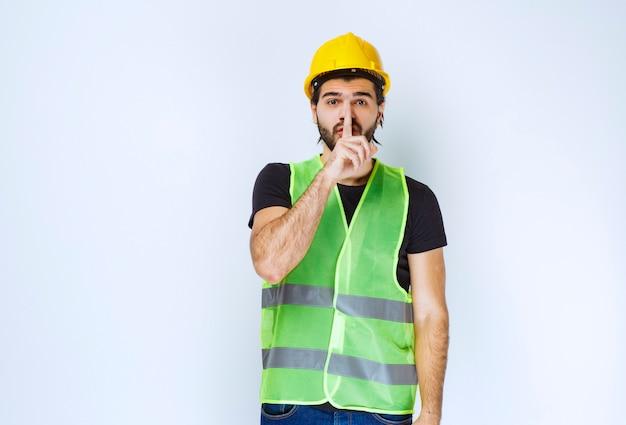 Man in gele helm die om stilte vraagt.