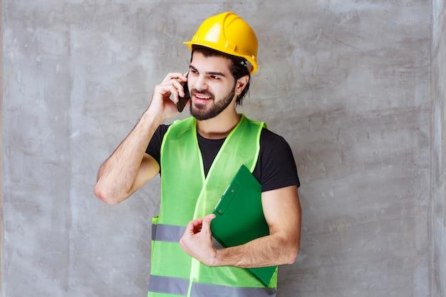 Man in gele helm en uitrusting die een rapportmap vasthoudt en tegen de telefoon praat