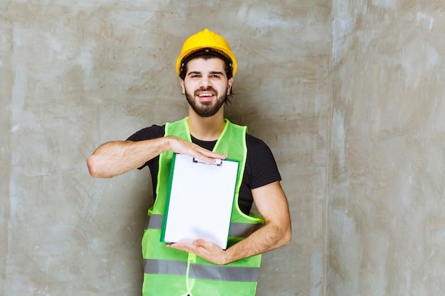 Man in gele helm en uitrusting met een projectplan en ziet er positief uit