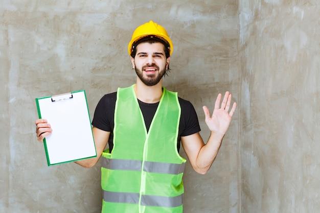 Man in gele helm en uitrusting met een projectplan en ziet er verward uit