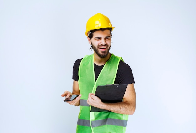 Man in gele helm met een projectmap en een smartphone.