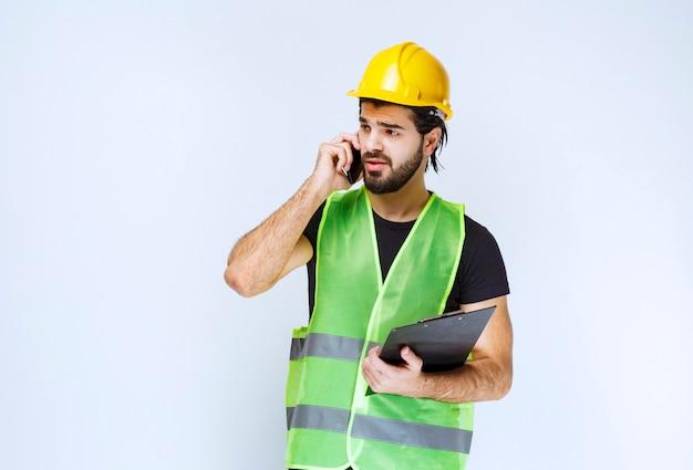 Man in gele helm praten aan de telefoon.