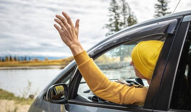 Man in gele hoed en trui rijdt in een auto langs de rivier en het prachtige herfstbos. concept van natuur, reizen en herfststemming