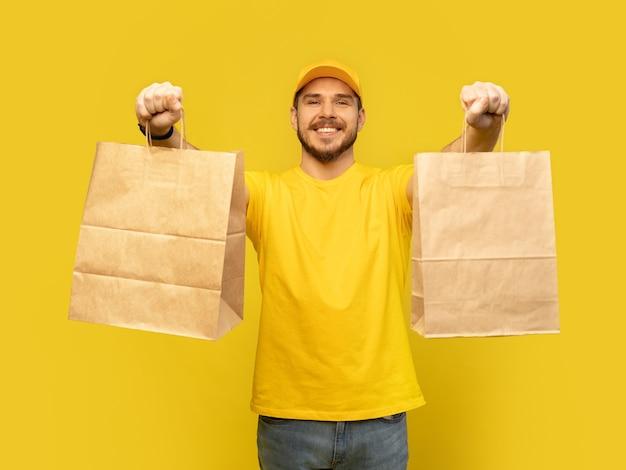 Man in gele pet, t-shirt met geïsoleerde papieren pakketten. mannelijke werknemerskoerier houdt papieren pakjes met voedsel vast