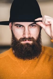 Man in gele ronde hals shirt met zwarte hoed