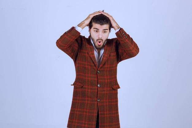 Man in geruite jas voelt zich erg verdrietig over iets en huilt.
