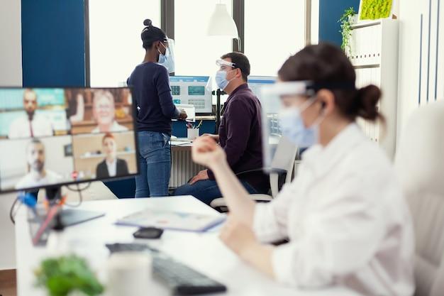 Man in gesprek met afrikaanse collega over een project op de werkplek met gezichtsmasker tegen covid. ondernemer met videogesprek terwijl collega's werken met respect voor sociale afstand tijdens wereldwijde pande