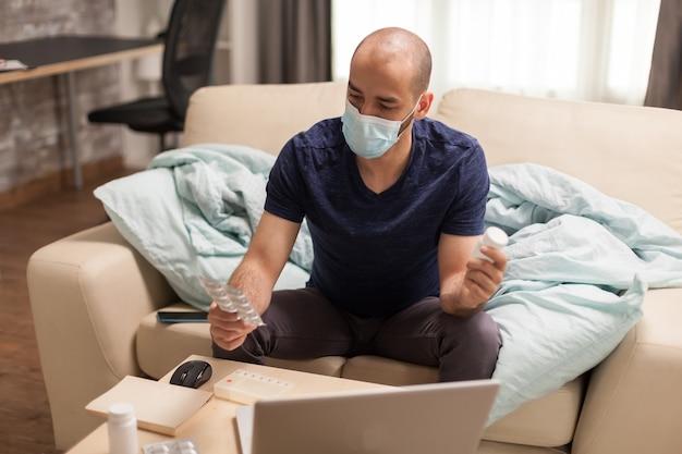 Man in gesprek met arts op laptop met pillenfles tijdens zelfisolatie.