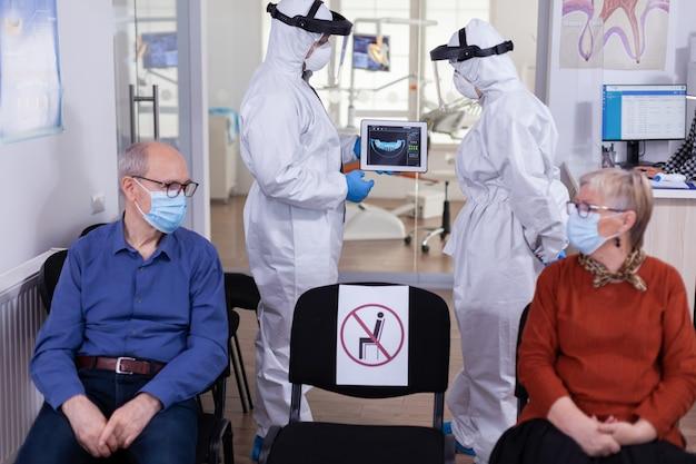 Man in gesprek met verpleegster in de tandheelkundige receptie die een beschermingspak draagt tegen het coronavirus, oudere patiënten die bij de receptie wachten en afstand houden