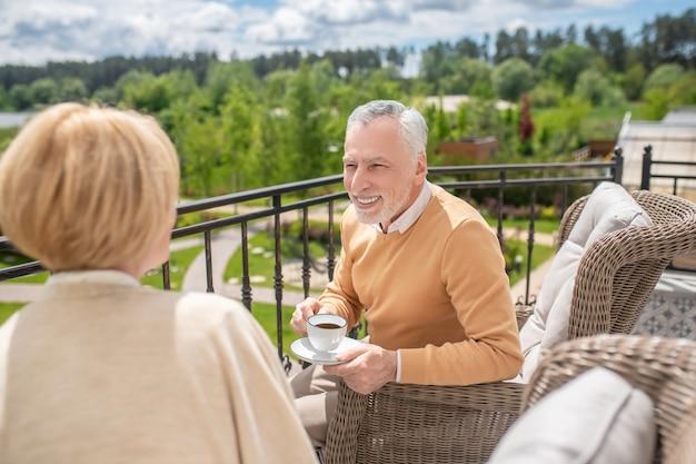 Man in gesprek met zijn vrouw op het terras