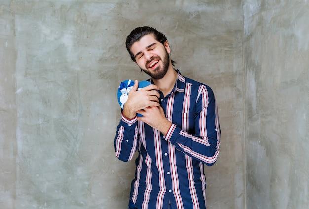 Man in gestreept shirt die een blauwe geschenkdoos in de vorm van een hart vasthoudt en hem knuffelt, voelt zich erg gelukkig