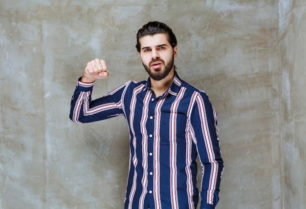 Man in gestreept shirt die haar vuisten laat zien en zich sterk voelt.