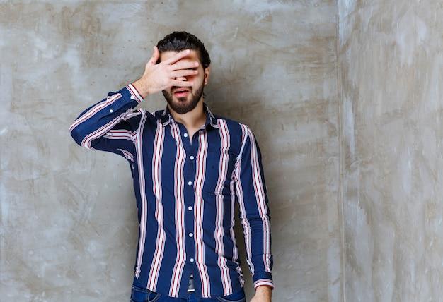 Man in gestreept shirt kijkt over vingers.