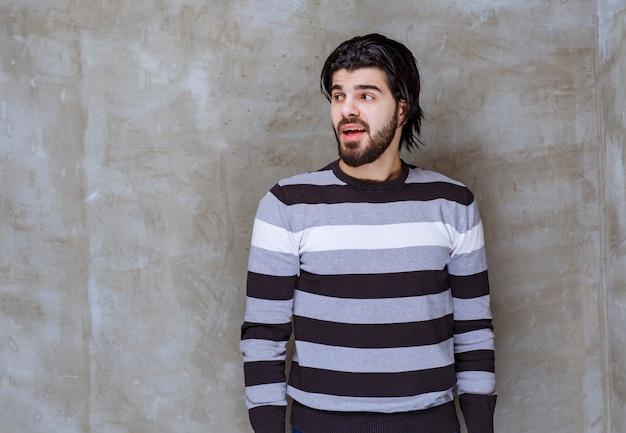 Man in gestreept shirt kijkt verbaasd en verward