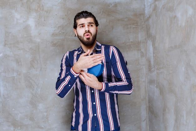 Man in gestreept shirt met een blauwe geschenkdoos en kijkt doodsbang