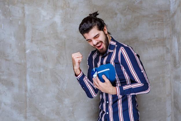 Man in gestreept shirt met een blauwe geschenkdoos in de vorm van een hart en voelt zich succesvol