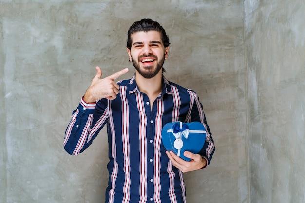 Man in gestreept shirt met een blauwe geschenkdoos in de vorm van een hart