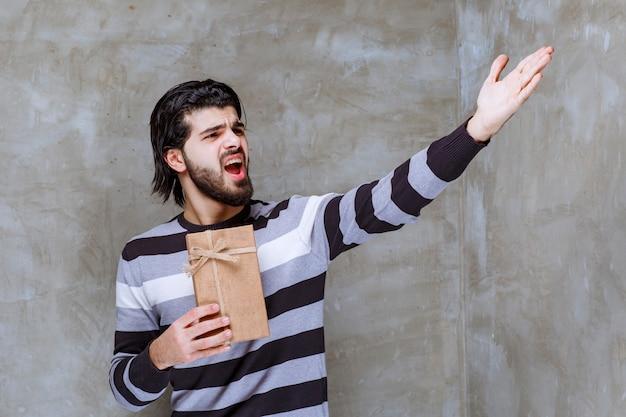 Man in gestreept shirt met een kartonnen geschenkdoos en ergens naar wijzend