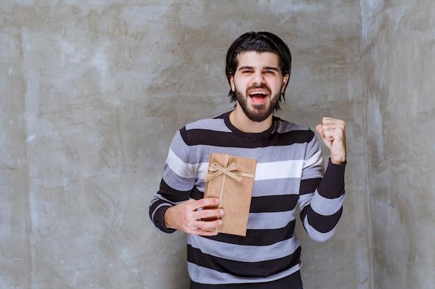 Man in gestreept shirt met een kartonnen geschenkdoos en zijn vuist tonend