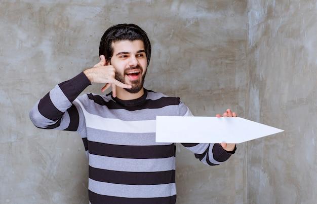 Man in gestreept shirt met een pijl die naar de rechterkant wijst en om een telefoontje vraagt