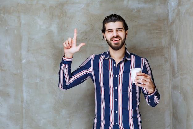 Man in gestreept shirt met een witte wegwerpbeker en denkt na over hoe hij het kan verkopen