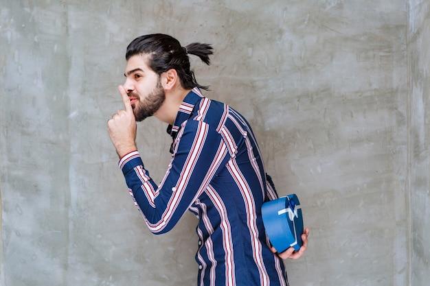 Man in gestreept shirt verbergt de blauwe geschenkdoos achter zichzelf