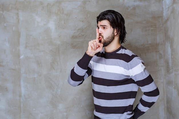 Man in gestreept shirt vraagt om stilte