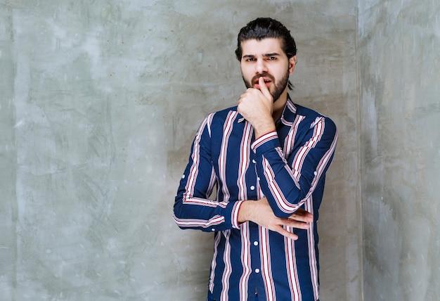 Man in gestreept shirt ziet er verward en attent uit.
