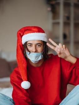 Man in gezichtsmasker en kerstman hoed poseren en camera thuis kijken