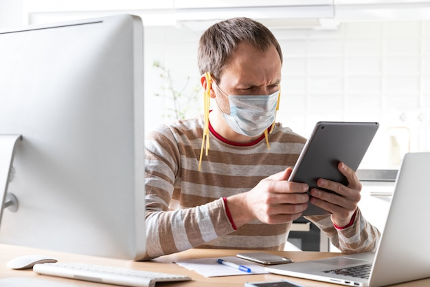 Man in gezichtsmasker met noedels op zijn oren, leest nep / breaking news op tablet