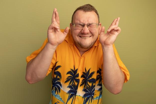Man in glazen die oranje overhemd dragen die wenselijke wens met gesloten ogen maken die vingers kruisen met hoopuitdrukking die zich over groene muur bevindt Gratis Foto