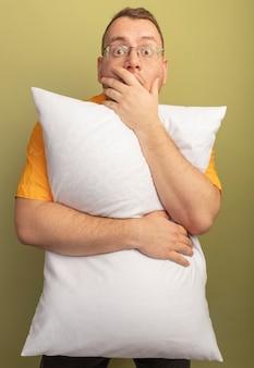 Man in glazen dragen oranje shirt knuffelen kussen wordt geschokt die mond bedekken met hand staande over lichte muur