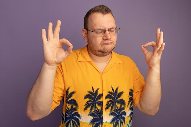 Man in glazen dragen oranje shirt meditatie gebaar maken met vingers met gesloten ogen permanent over paarse muur