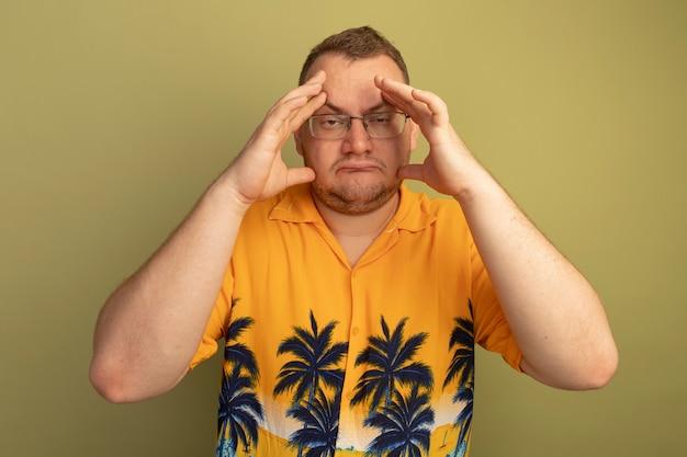Man in glazen dragen oranje shirt onwel aanraken van zijn hoofd met sterke hoofdpijn staande over groene muur