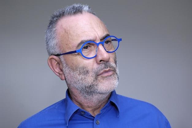 Man in glazen en blauw shirt staren,