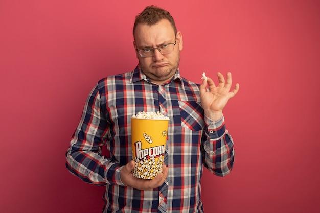 Man in glazen en geruit overhemd met emmer met popcorn die ontevreden is met een fronsend gezicht dat zich over de roze muur bevindt