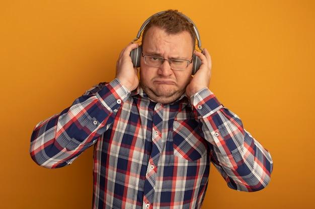 Man in glazen en geruit overhemd met koptelefoon met fronsend gezicht dat zich over oranje muur bevindt