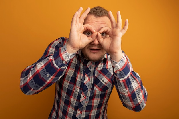 Man in glazen en ingecheckte shirt door vingers verrekijker gebaar staande over oranje muur maken