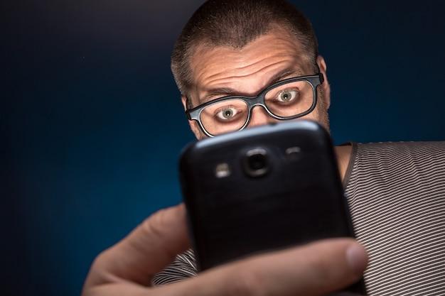 Man in glazen kijkt naar zijn smartphone