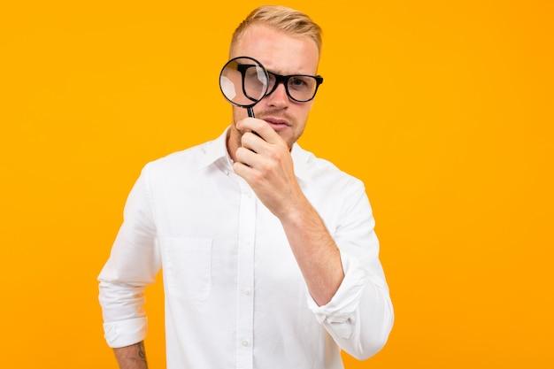 Man in glazen met een vergrootglas in een wit overhemd op geel