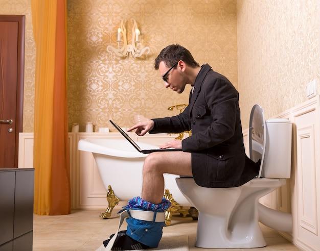 Man in glazen met laptop zittend op de wc-pot