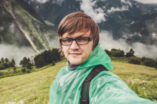Man in glazen selfie met groen gras bergen