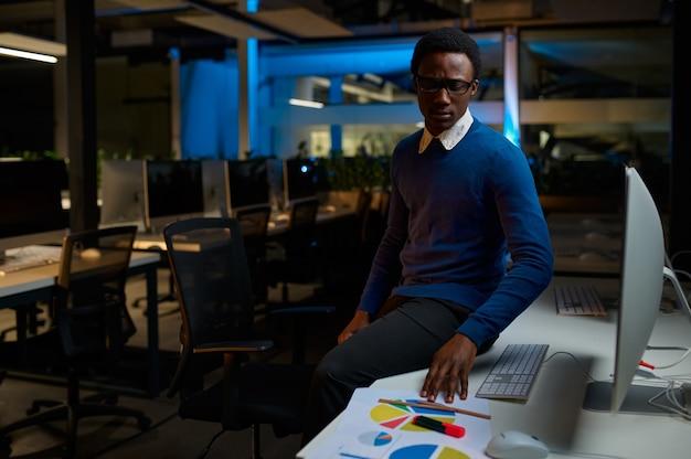 Man in glazen werkt op computer, kantoor levensstijl. mannelijke persoon op desktop, donker interieur, moderne werkplek