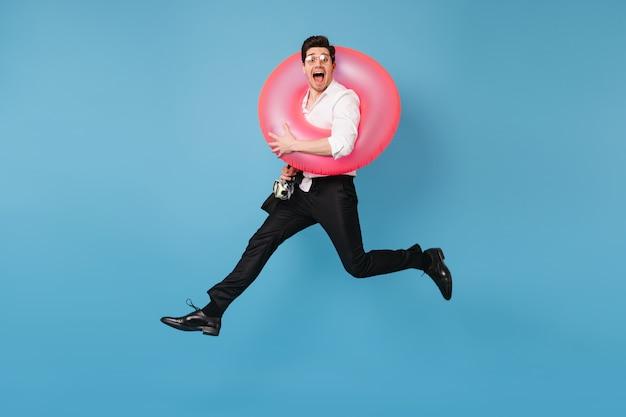 Man in goed humeur springt tegen blauwe ruimte met roze rubberen ring. portret van vrolijke kerel in bureauuitrusting.