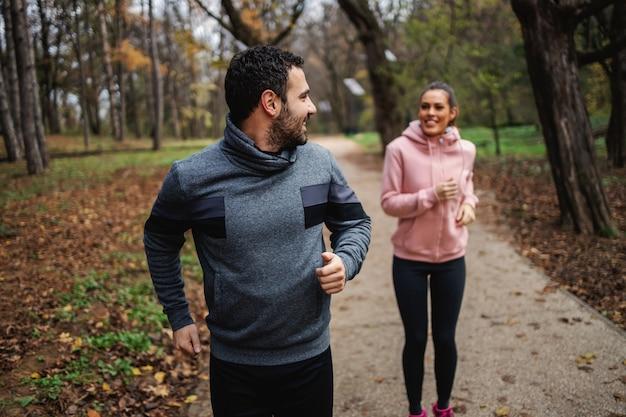 Man in goede vorm loopt snel in de herfst en kijkt naar zijn vriendin die hem probeert in te halen.