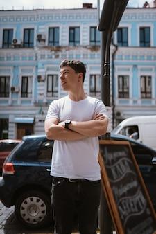 Man in grijs t-shirt en spijkerbroek over stadsstraat