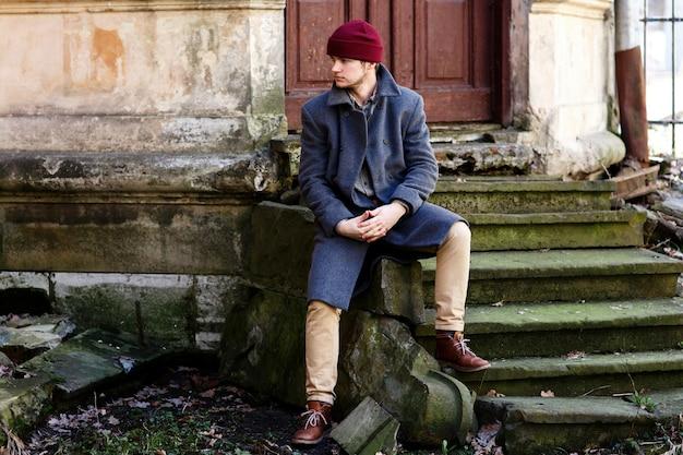 Man in grijze jas en beige broek zit op stenen voetstappen