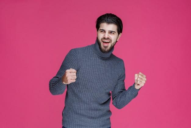 Man in grijze trui demonstreert zijn vuisten en voelt zich krachtig.